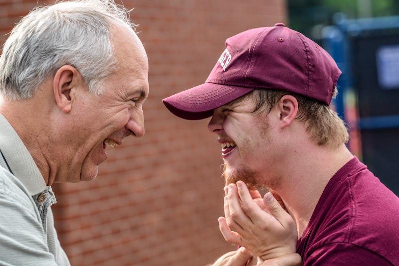 Älterer Mann und Jugendlicher mit Down Syndrom lachen zusammen